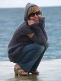 Senhora de Youn na capa que senta-se perto do mar Imagens de Stock