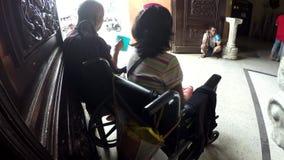 Senhora deficiente na cadeira de rodas com outros mendigos masculinos no portal da porta da igreja filme