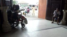 Senhora deficiente na cadeira de rodas com outros mendigos masculinos no portal da porta da igreja vídeos de arquivo