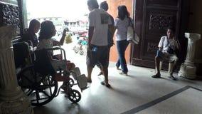 Senhora deficiente na cadeira de rodas com outros mendigos masculinos no portal da porta da igreja video estoque