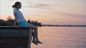 A senhora delgada nova é sentar-se à superfície da àgua no fulgor do por do sol do verão e relaxar video estoque