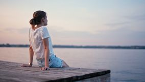 A senhora delgada nova está apreciando o fulgor do por do sol do verão perto do lago e está relaxando filme