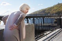 Senhora deprimida que resiste a dor lombar fora Imagem de Stock Royalty Free