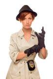 Senhora Detetive Puts em suas luvas no revestimento de trincheira no branco Imagem de Stock Royalty Free