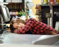 Senhora do caixa que dorme no espaço de trabalho na loja do supermercado imagem de stock