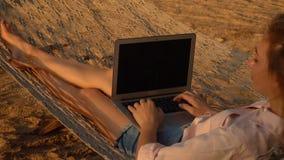 Senhora do escritor do movimento lento que trabalha no portátil que encontra-se na rede filme