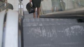 A senhora do negócio com um saco em sua mão monta acima da escada rolante video estoque
