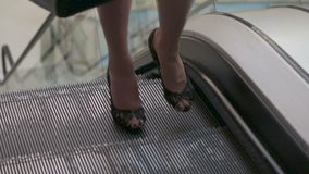 A senhora do negócio com um saco em sua mão monta acima da escada rolante filme