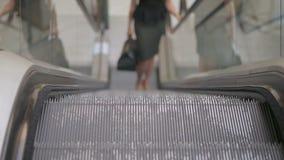A senhora do negócio com um saco em sua mão monta acima da escada rolante vídeos de arquivo
