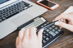 Senhora do negócio da manhã Mãos fêmeas com uma pena e uma calculadora, em que milhão são contados O fundo é um smartphone e Foto de Stock
