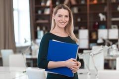 A senhora do negócio está no escritório com um dobrador nas mãos Fotos de Stock