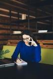 A senhora do negócio fala no telefone e faz anotações na tabela de trabalho Foto de Stock
