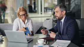 Senhora do negócio maduro que discute a informação com o homem farpado no café moderno video estoque