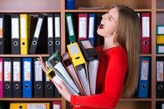 Senhora do negócio que guarda a grande pilha de dobradores do escritório Imagem de Stock Royalty Free