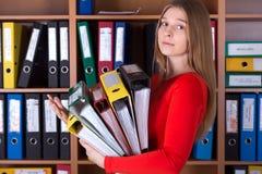 Senhora do negócio que guarda a grande pilha de dobradores do escritório Fotos de Stock