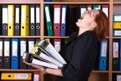 Senhora do negócio que guarda a grande pilha de dobradores do escritório Imagens de Stock Royalty Free