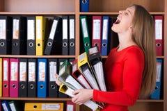 Senhora do negócio que guarda a grande pilha de dobradores do escritório Fotografia de Stock Royalty Free