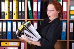 Senhora do negócio que guarda a grande pilha de dobradores do escritório Foto de Stock
