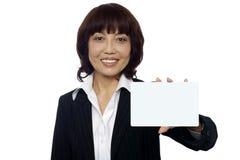Senhora do negócio que mostra o cartaz em branco à câmera Imagens de Stock