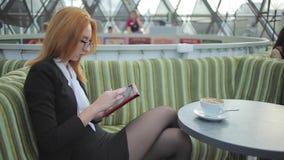 Senhora do negócio que trabalha em uma tabuleta no Cafee video estoque