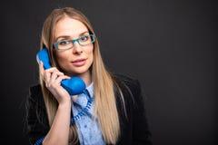 Senhora do negócio que veste os vidros azuis que falam no receptor azul imagens de stock royalty free