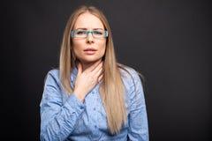 A senhora do negócio que veste os vidros azuis que guardam a garganta gosta de ferir imagem de stock royalty free