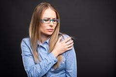 A senhora do negócio que veste os vidros azuis que guardam o ombro gosta de ferir fotografia de stock
