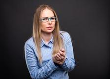 A senhora do negócio que veste os vidros azuis que guardam o pulso gosta de ferir imagens de stock
