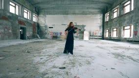 A senhora do ruivo está andando ao longo do salão ao jogar o violino filme