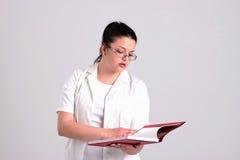 A senhora Doctor na roupa de Clinicall está lendo diagnostica o livro imagem de stock royalty free