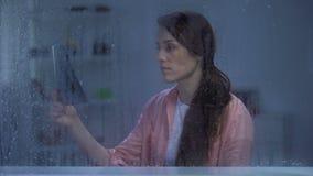 A senhora doente da morte que olha nos pulmões radiografa atrás da janela chuvosa, nenhuma esperança para a recuperação filme