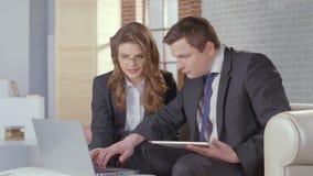 A senhora e o homem do negócio verificam a apresentação no portátil, movimento lento filme