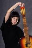 Senhora elegante bonita que veste um vestido preto gótico com colar alto, poses com uma guitarra acústica em um cinza fotografia de stock
