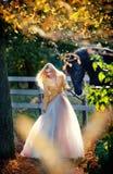 Senhora elegante com o vestido nupcial branco perto do cavalo preto na floresta Fotografia de Stock