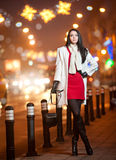 A senhora elegante que veste o vestido vermelho e o revestimento branco exteriores no cenário urbano com cidade ilumina-se no fund Fotos de Stock