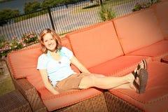 Senhora em férias no sofá da área da piscina Imagem de Stock