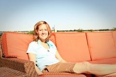 Senhora em férias no sofá da área da piscina Foto de Stock