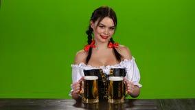 A senhora em ofertas bávaras do traje bebe dois vidros da cerveja Tela verde filme