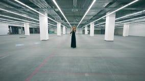 A senhora em um vestido preto está jogando o violino em um salão vazio filme