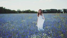 A senhora encantador em um vestido de casamento leve branco longo com as luvas curtos de um decote profundo e do programa, menina filme
