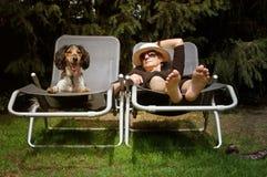 Senhora engraçada que sunbathing com seu cão Fotos de Stock Royalty Free