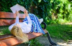 Senhora esperta que relaxa A menina coloca o parque do banco que relaxa com livro, fundo verde da natureza A mulher gasta o lazer imagens de stock royalty free
