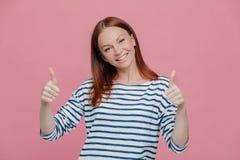 A senhora europeia bonita nova feliz para dar acima o polegar dobro, gosta de alguém ideia ou dá a aprovação, vestida em equipame fotografia de stock royalty free