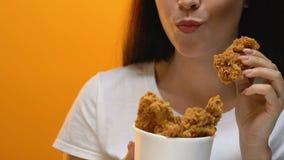 Senhora feliz que come o frango frito friável da cubeta, fast food para viagem, fim acima vídeos de arquivo