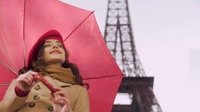 Senhora feliz que está sob o guarda-chuva que sorri aos transeuntes que esperam seu amigo video estoque