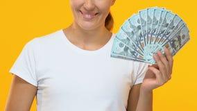 Senhora feliz que guarda o grupo dos dólares e que mostra os polegares acima, o salário e os benefícios video estoque