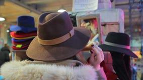 Senhora glamoroso que põe sobre o chapéu brimmed largo, levantando, tendo o divertimento no mercado local video estoque