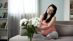 Senhora grávida bonita que decora a casa com flores agradáveis, apreciação estética fotos de stock