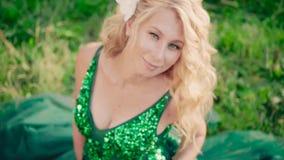 Senhora grávida com as orquídeas brancas no cabelo louro, sentando-se na grama em um vestido verde lindo longo com esmeralda vídeos de arquivo