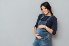 Senhora grávida feliz que está sobre o fundo cinzento imagens de stock royalty free
